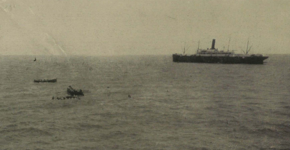 Boats picking up men in the water