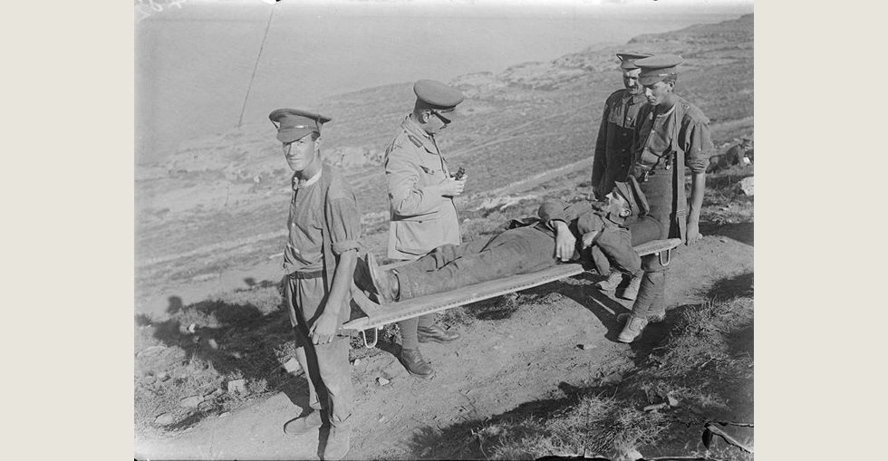 Brigadier-General Felix Frederic Hill, the Commander of the 31st Brigade (10th Irish Division), speaking to a man wounded by shrapnel who is being taken away on a stretcher