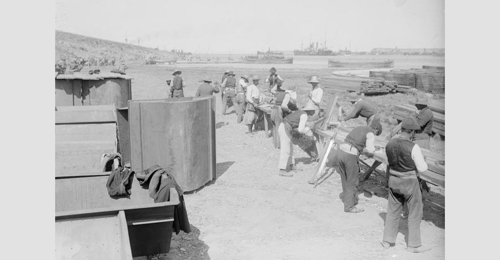 Civilian carpenters at work at Mudros. In the background the shipping in the harbour can be seen.