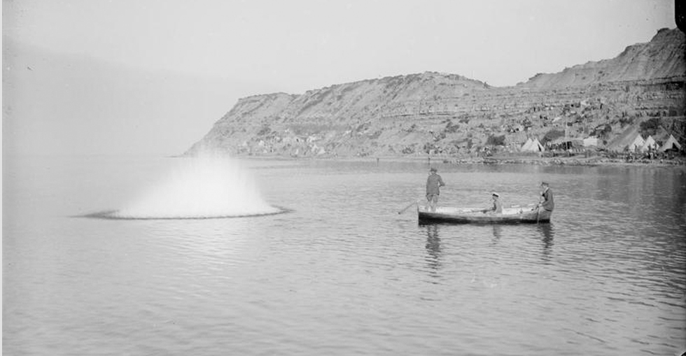 Officers in a small boat using grenades to stun fish off Cape Helles