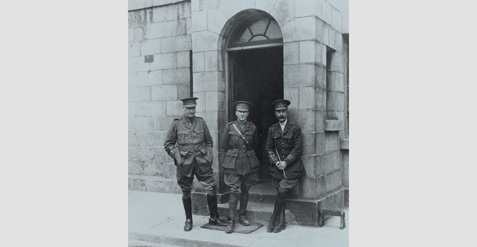 Three of the soldiers stand at a doorway in the Royal Barracks