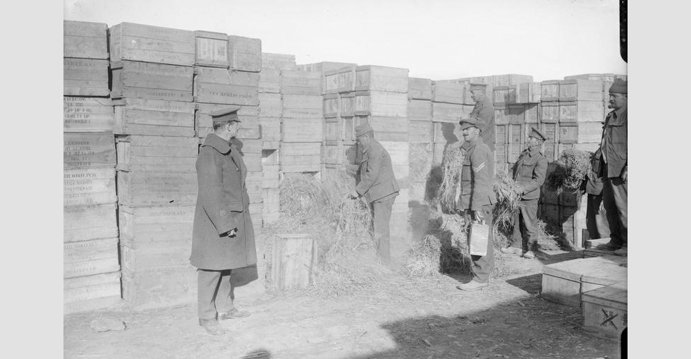 Hay and petrol being placed among the boxes of stores in a dump at 'A' West Beach, Suvla Point, to be burnt on evacuation, December 1915.