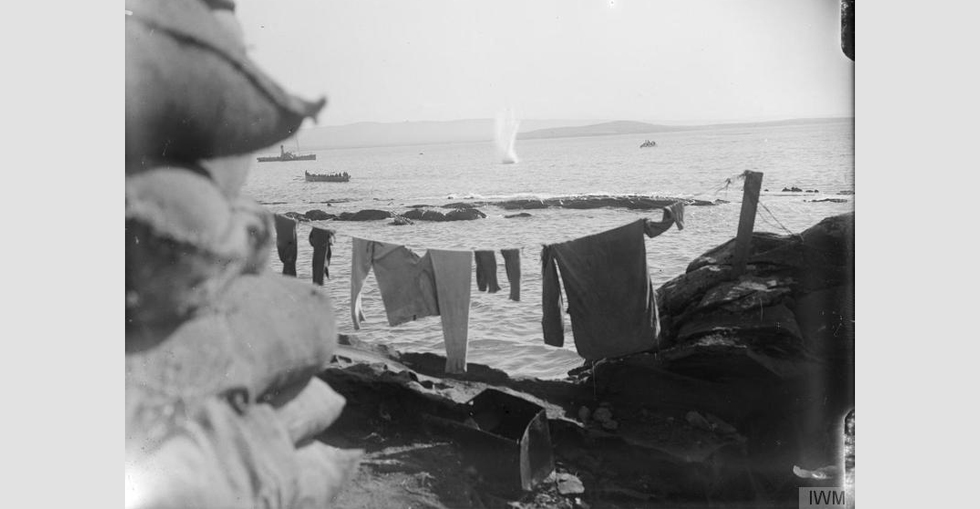A shell from a Turkish battery plunging into the sea at the Dardanelles, after missing its target - the boat load of troops to the left. Note the laundry drying up in the foreground.