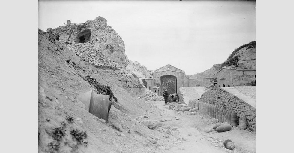 A view of the old port at Sedd el Bahr, Cape Helles, showing damage caused by the naval bombardments prior to the Gallipoli landings in 1915. A British soldier stands on sentry amongst the ruins of the old gate.