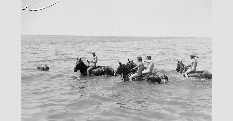 Soldiers taking their horses into the sea.