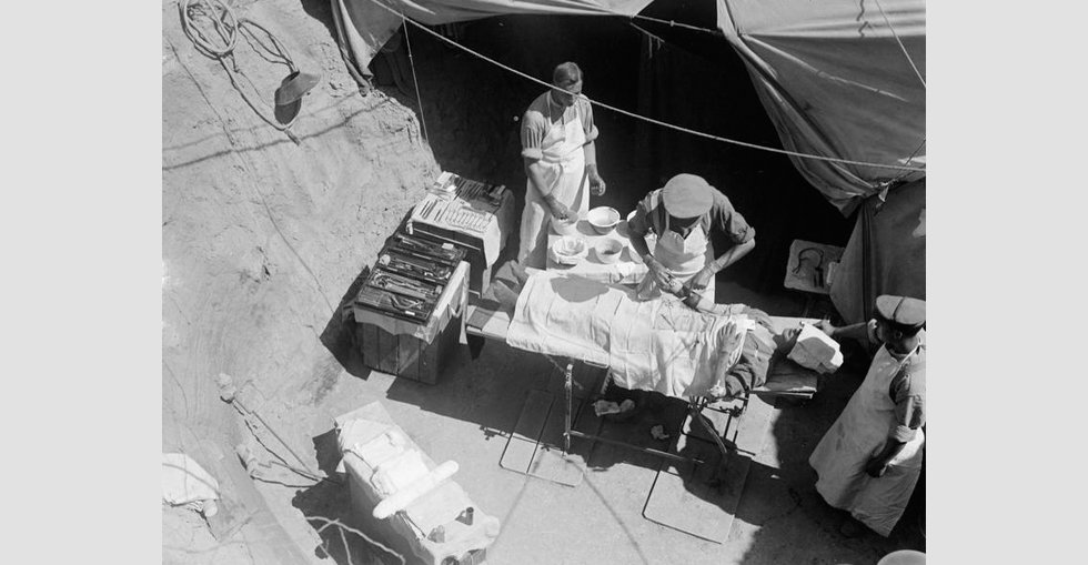 A surgeon is removing a bullet from the patient's right arm in the operation dugout of the Field Ambulance of the 42nd (East Lancashire) Division.