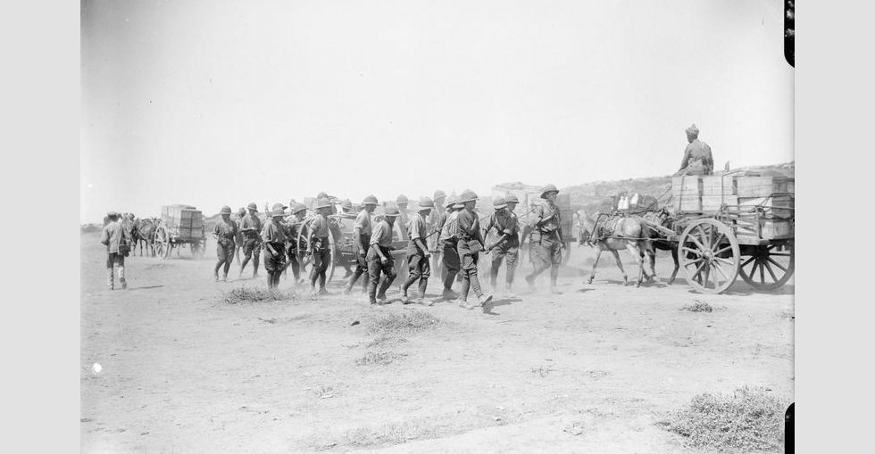 Troops hauling a water cart and Indian ammunition transport carts with stores at Suvla Bay.
