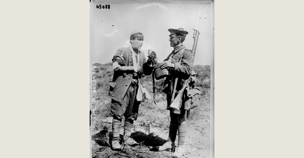 English soldier giving water to a Turkish prisoner
