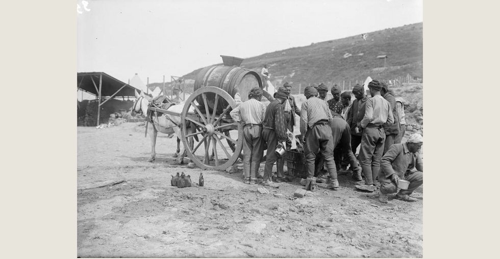 Turkish prisoners, captured during the Gallipoli campaign, drawing water from a water-cart in the French Sector of V Beach at Sedd el Bahr, Cape Helles.