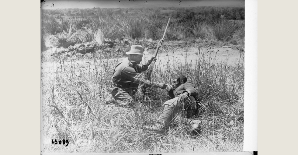 English soldier giving water to a wounded Turkish